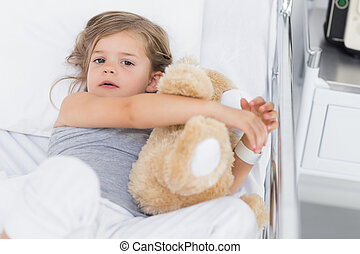 Cute girl hugging teddy bear in hospital bed - High angle...