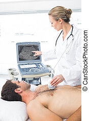 Doctor using sonogram on male patient - Female doctor using...