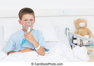 Boy wearing oxygen mask in hospital - Portrait of sick boy...
