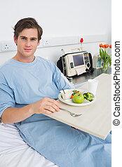 Man in gown having mean in hospital - Portrait of man in...