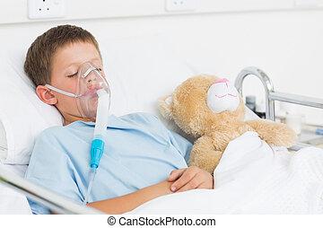 Boy wearing oxygen mask sleeping beside teddy bear - Sick...