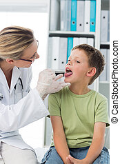 Doctor looking at the mouth of boy - Female doctor looking...