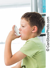 Boy using asthma inhaler in hospital - Side view of little...