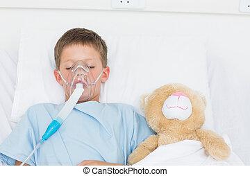 Boy wearing oxygen mask sleeping beside stuffed toy - Sick...