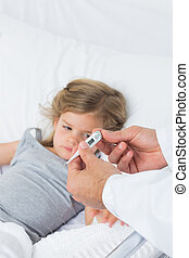 Doctor holding thermometer with ill girl in hospital