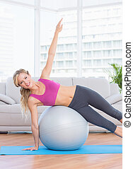 Happy fit blonde doing side plank with exercise ball at home...