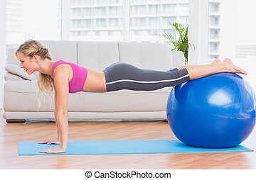 Slim blonde in plank position using exercise ball at home in...