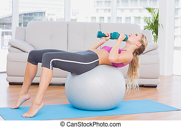 Smiling blonde doing sit ups with exercise ball holding...