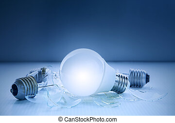 abstract of led light bulb glowing and lyinjg with another...