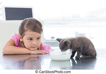Girl looking at kitten drinking mil - Little girl looking at...