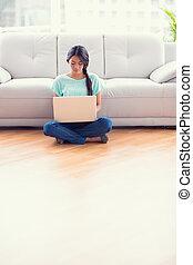 Pretty girl sitting on a floor usin