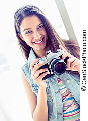 Smiling young woman holding her camera in a bright room