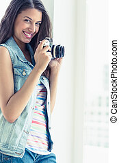 Stylish young woman taking a photo smiling at camera in a...