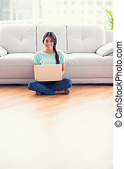 Pretty girl sitting on a floor using laptop smiling at camera