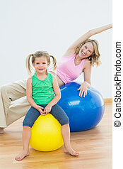 Happy pregnant woman exercising on exercise ball with young daughter in a fitness studio