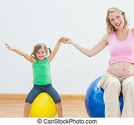 Happy pregnant woman bouncing on exercise ball with young daughter in a fitness studio