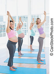 Smiling pregnant women in yoga class standing in tree pose...
