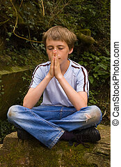 Young boy praying - a young poorly dressed caucasian boy sat...