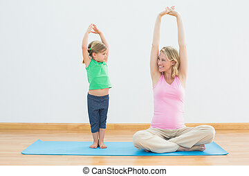 Pregnant smiling mother and daughter doing yoga together in...