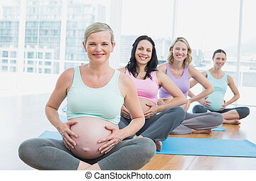 Pregnant women in yoga class sitting on mats touching their...