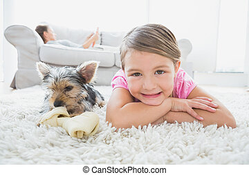 Little girl lying on rug with yorkshire terrier smiling at...