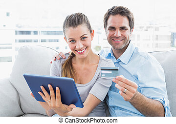 Happy couple sitting on the couch shopping online with tablet pc at home in the living room