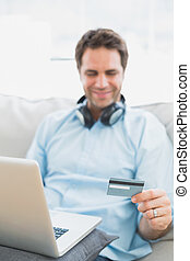 Smiling handsome man sitting on sofa online shopping with laptop at home in the living room