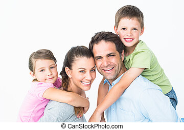 Cheerful young family looking at camera together on white...
