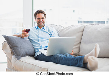 Smiling handsome man relaxing on sofa with glass of red wine...