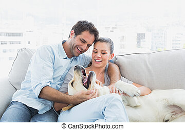 Happy couple petting their yellow labrador on the couch at...