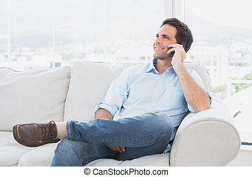 Cheerful man sitting on the couch making a phone call