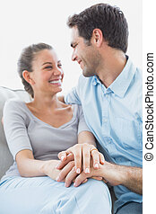 Excited couple looking at each other on the couch
