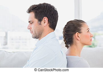 Unhappy couple sitting back to back on the couch at home in...
