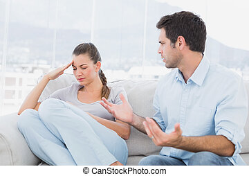 Man pleading with his upset partner on the couch at home in...