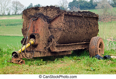 Muck Spreader - an old well used muck spreader parked on a...