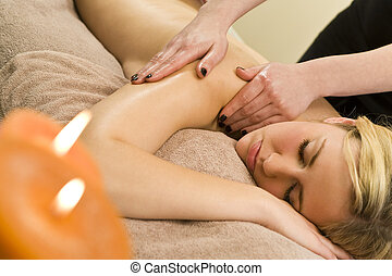 Candlelit Massage - A young woman relaxing at a health spa...