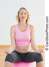 Peaceful blonde pregnant woman sitting on exercise ball
