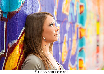 worried young woman - sad young woman leaning on wall and...