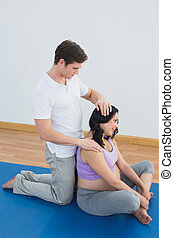 Masseur massaging pregnant womans shoulder and neck in a...