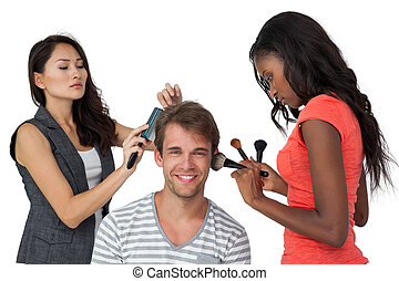 Assistants applying make-up to male model over white...