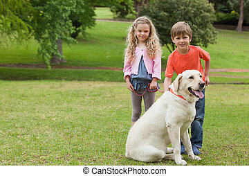 Two kids with pet dog at park - Full length portrait of two...