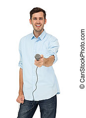 Portrait of a young man holding out microphone