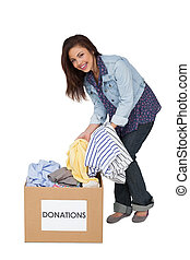 Portrait of a happy young woman with clothes donation...