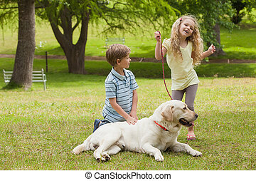 Two happy kids with pet dog at park