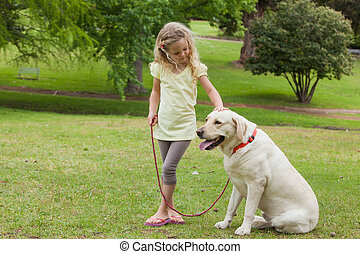 Young girl with pet dog at park - Full length of a young...
