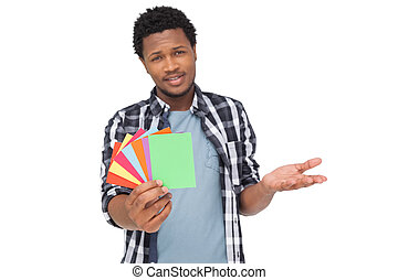 Portrait of a confused man holding colorful papers