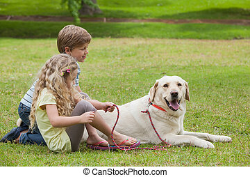 Two kids with pet dog at park