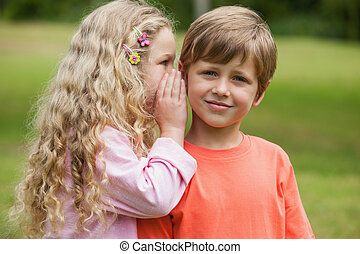 Girl whispering secret into boys ear at park - Young girl...