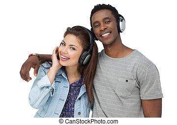 Portrait of a young couple enjoying music over white...