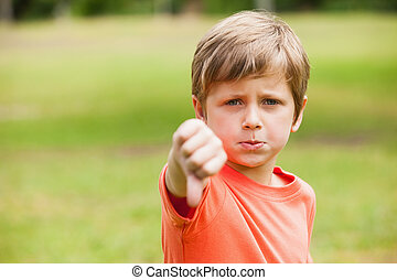 Boy gesturing thumbs down at the park - Portrait of a young...